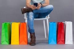 供以人员坐与五颜六色的购物袋的一把椅子和使用手机 库存照片