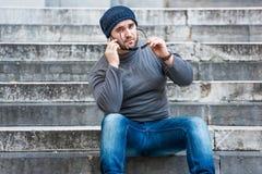 供以人员坐台阶和谈话在电话-看照相机 免版税库存图片