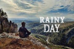 供以人员坐在山,它顶部的远足者是湿恶劣天气 雨天字法由云彩制成 图库摄影
