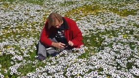 供以人员坐在拍与他的手机的花的领域照片 图库摄影