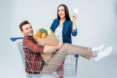 供以人员坐在有显示空插件的食品杂货袋和微笑的妇女的购物车 免版税库存照片