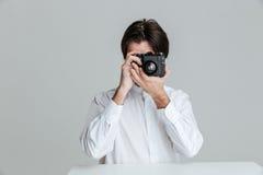 供以人员坐在桌上和做与照相机的照片 库存照片