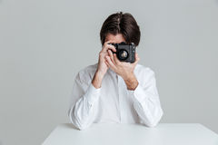 供以人员坐在桌上和做与照相机的照片 免版税库存照片