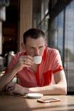 供以人员坐在桌上的饮用的咖啡由窗口 免版税库存图片