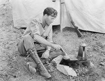 供以人员坐在他的准备食物的帐篷前面(所有人被描述不更长生存,并且庄园不存在 供应商warran 免版税库存图片