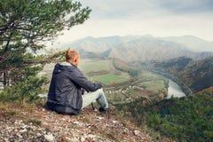 供以人员坐在mountaine谷上的峭壁边缘 免版税库存图片