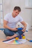 供以人员坐地板和看在颜色取样器的画家 库存图片