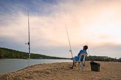 供以人员坐并且等待与金黄天空的渔 图库摄影