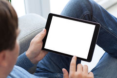 供以人员坐拿着有被隔绝的屏幕的沙发片剂计算机 免版税图库摄影
