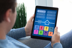 供以人员坐拿着片剂计算机app聪明的家的沙发 免版税库存照片