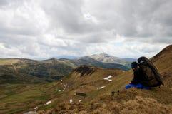 供以人员坐有美丽的一个山草甸 免版税图库摄影