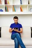 供以人员坐沙发和使用片剂个人计算机 库存图片