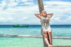 供以人员基于在海洋背景的一棵棕榈树  免版税图库摄影