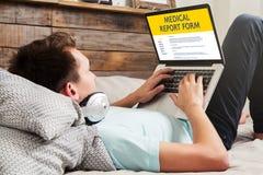 供以人员填写在便携式计算机的一个医疗报告形式 免版税库存图片