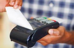 供以人员处理付款的佩带的蓝色白方块样式衬衣使用在照相机,特写镜头前面的信用卡终端 库存照片