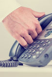 供以人员夹住一副受话器在他的手上 库存照片