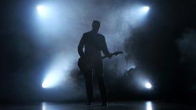 供以人员奏起在吉他的一个缓慢的声调 烟演播室 股票视频