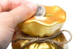 供以人员安置一枚欧洲硬币入存钱罐 免版税图库摄影