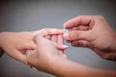 供以人员安置金刚石定婚戒指在他的未婚夫的手指 库存照片