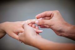 供以人员安置金刚石定婚戒指在他的未婚夫的手指 免版税库存照片