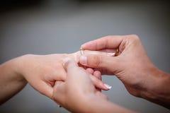 供以人员安置金刚石定婚戒指在他的未婚夫的手指 免版税库存图片