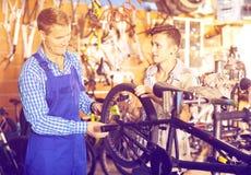 供以人员工作与自行车车轮和帮助的男孩 免版税库存照片