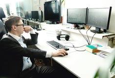 供以人员工作在一台计算机在有显示器的办公室 免版税库存图片