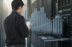 供以人员工作在数据中心并且使用片剂为分析系统 免版税库存照片