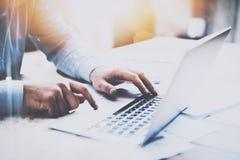 供以人员工作在木桌上在现代顶楼办公室 在工作场所供以人员坐和键入在膝上型计算机键盘 蠢材 免版税库存图片