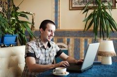 供以人员工作在膝上型计算机的一个咖啡馆 库存图片
