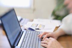 供以人员工作在键盘的膝上型计算机手上 库存图片