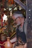 供以人员工作黏土在à 维拉的中世纪市场上 库存图片