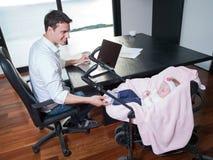 供以人员工作从家并且照顾婴孩 免版税库存图片