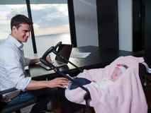供以人员工作从家并且照顾婴孩 图库摄影