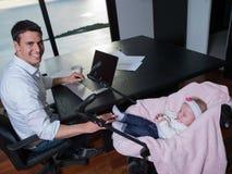 供以人员工作从家并且照顾婴孩 库存图片