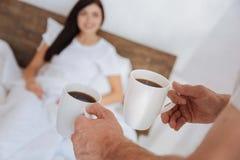 供以人员带来咖啡给他的女朋友在床上 免版税图库摄影