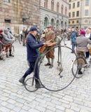 供以人员带领一辆非常老自行车和佩带古板的花呢 免版税库存照片