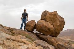 供以人员常设近的辗压圆的大岩石在山边缘 免版税图库摄影