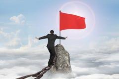 供以人员平衡在旗子的生锈的链子在山上面 免版税库存照片