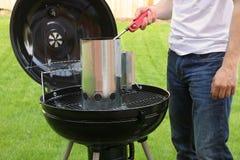 供以人员开始BBQ煤炭与打火机的烟囱火 免版税图库摄影