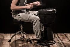 供以人员弹一个djembe鼓和铙钹在黑背景 免版税图库摄影