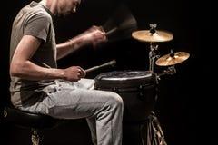 供以人员弹一个djembe鼓和铙钹在黑背景 免版税库存照片