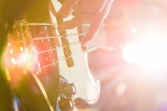 供以人员弹在黑色和黄色的低音吉他 免版税图库摄影