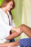供以人员得到膝盖治疗从理疗的治疗师,她的握他的腿和申请按摩,伤害医疗概念的手 免版税图库摄影