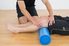 供以人员得到他的膝盖审查由一位理疗师 图库摄影
