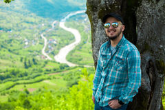 供以人员微笑,并且摆在与山的树附近从b环境美化 免版税库存照片