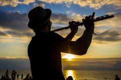 供以人员戏剧长笛在海滩的日落在海岛酸值Phangan,泰国的一个满月党期间 免版税库存照片