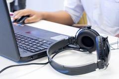 供以人员手使用键盘和老鼠控制有headpho的膝上型计算机 库存照片