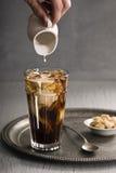 供以人员手倾吐奶油入杯被冰的咖啡 库存照片