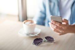 供以人员手在智能手机的正文消息在咖啡馆 库存照片